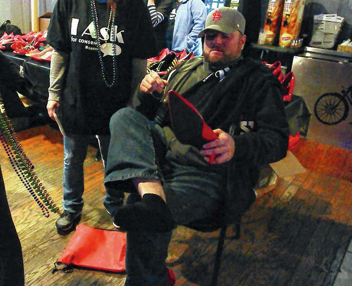 Eric Niehaus of Springfield finds a pair of high-heeled shoes Saturday in preparation for the Walk a Mile in Her Shoes march.