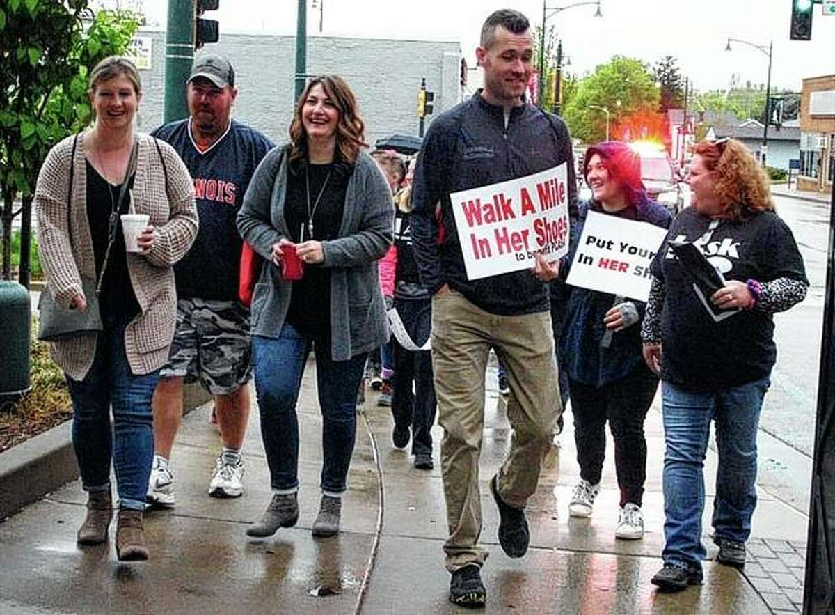 Amy Joy (right) and Luke Poore lead the Walk a Mile in Her Shoes march Satuday from the Handle Bar and around the downtown square.