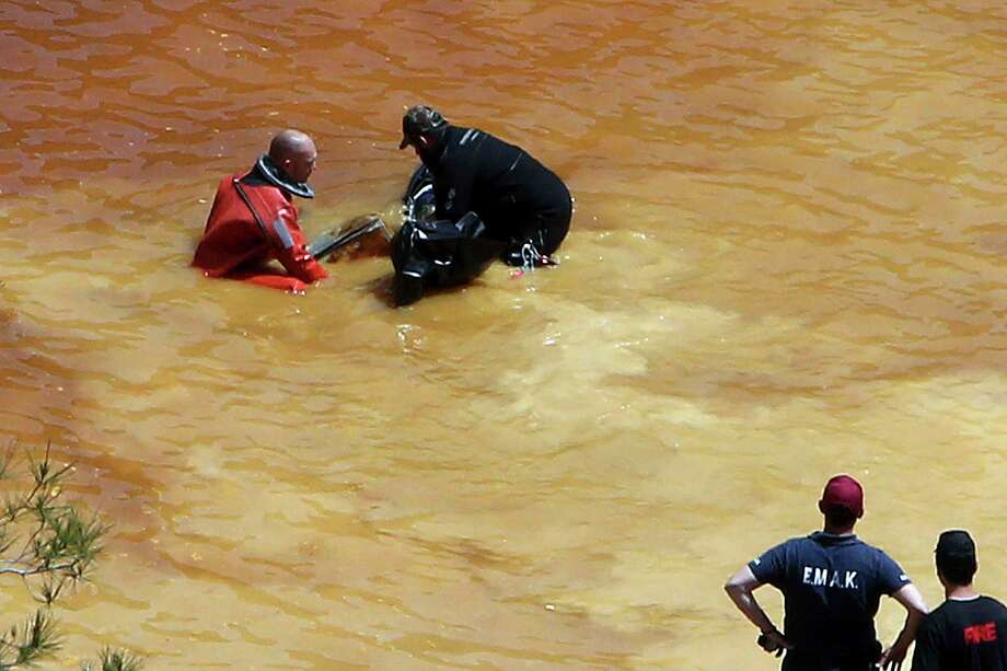 A diver, left, and an Investigator remove a suitcase found in a man-made lake, near the village of Mitsero outside of the capital Nicosia, Cyprus, Sunday, April 28, 2019. A travel suitcase containing the decomposing remains of an adult woman and a concrete block was retrieved from the bottom of a man-made lake, the chief of Cyprus' Criminal Investigation Department said Sunday. The woman is believed to be one of the victims of a Cypriot military officer who has confessed to killing seven foreign women and girls. Photo: Petros Karadjias, AP / Copyright 2019 The Associated Press. All rights reserved.