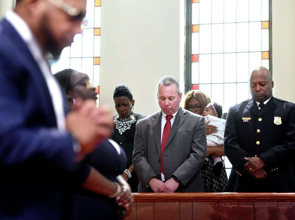 Hamden Acting Police Chief John Cappiello (center) and New Haven Police Captain Anthony Duff (right) bow their heads as Deon Kipping (far left) and Erica Williams (left) lead the congregation in songs of worship at Varick Memorial AME Zion Church in New Haven during the Hope for Healing Community Prayer Service on April 28, 2019.