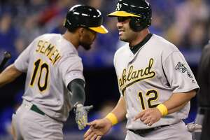 Oakland Athletics designated hitter Kendrys Morales (12) celebrates with teammate Marcus Semien (10) after scoring a run against the Toronto Blue Jays during 11th-inning baseball game action in Toronto, Sunday, April 28, 2019. (Frank Gunn/The Canadian Press via AP)
