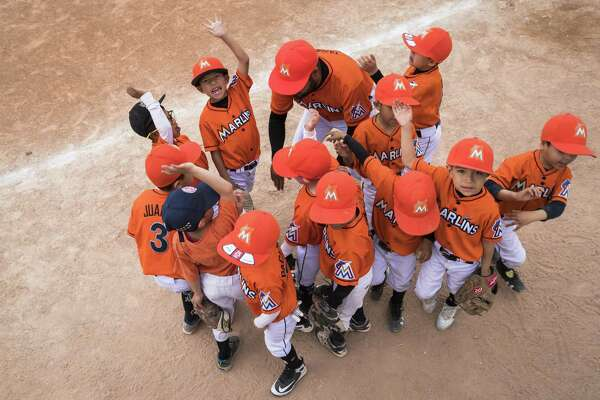 The Little League team called Marlins based in Ciudad Juárez gather in a hurdle and cheer the beginning of the game against the Angels on April 5 in Ciudad Juárez. Memo Garcia, who lives in El Paso, commutes here twice a week to play on the team. Delays at the ports of entry have made cross-border travel grueling.