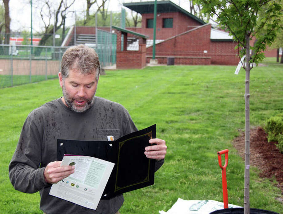 Edwardsville Mayor Hal Patton reads his Arbor Day remarks during a short but damp tree planting ceremony at the Edwardsville Children's Museum Saturday. At right is the new tree, a Red-Pointe Maple. Photo: Charles Bolinger | The Intelligencer