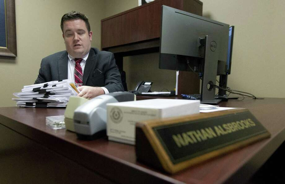Montgomery County Assistant District Attorney Nathan Alsbrooks moves warrents he is working on in his office, Thursday, April 25, 2019, in Conroe. Alsbrooks, who is legally blind, currently approves arrest warrants for the District Attorney's Office. Photo: Jason Fochtman, Houston Chronicle / Staff Photographer / © 2019 Houston Chronicle