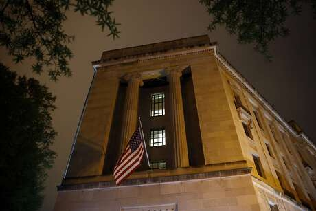 An American flag flies outside the Department of Justice early Thursday, April 18, 2019, in Washington. The Justice Department on Thursday is expected to release a redacted version of special counsel Robert Mueller's report on Russian election interference and President Donald Trump's campaign. (AP Photo/Patrick Semansky)