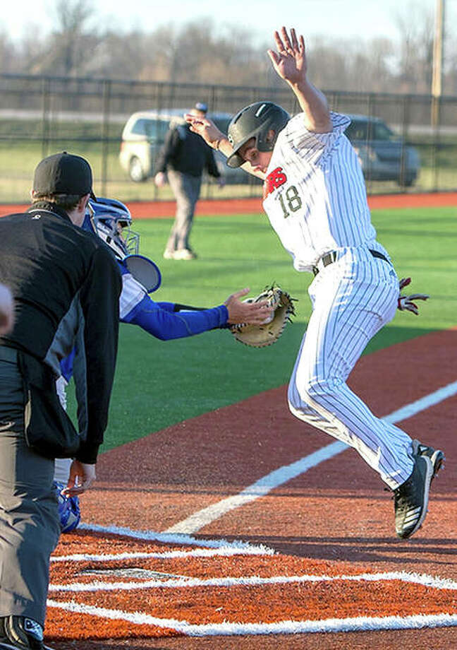SIUE's Justin Perkin, right, tries to avoid being tagged out at home plate in a 2-0 win over Saint Louis University March 26 at SIUE. The teams will square off again at 6 p.m. Tuesday at Saint Louis U. Photo: SIUE Athletics