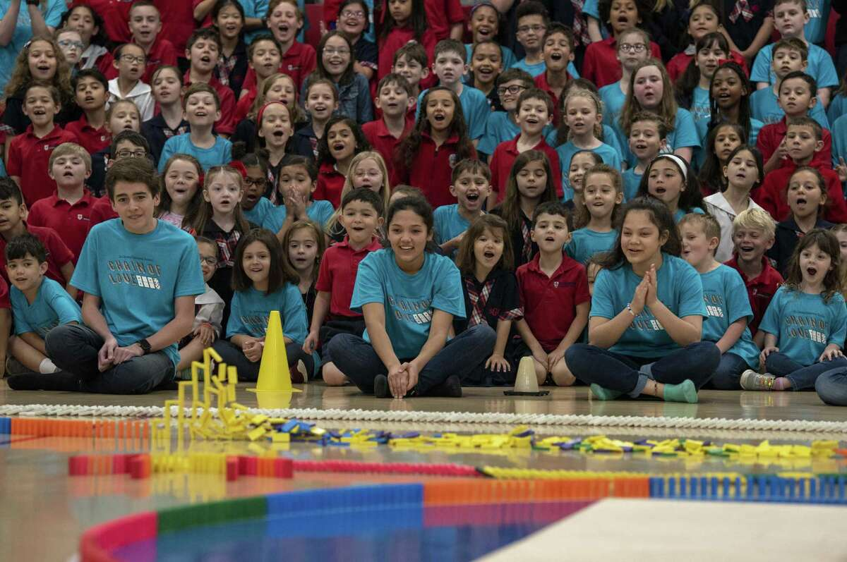 Excited students at St. George Episcopal School, including Sammy Salter, in front from left, Macie Lin and Kaia Pham, watch Monday morning as 30,000 dominoes fall through a complex series of patterns on the gym floor as part of its annual Chain of Love, which has grown from 3,500 dominoes 14 years ago. The event raises money for their sister school, St. Benoit, in Mombin Crochu, Haiti.