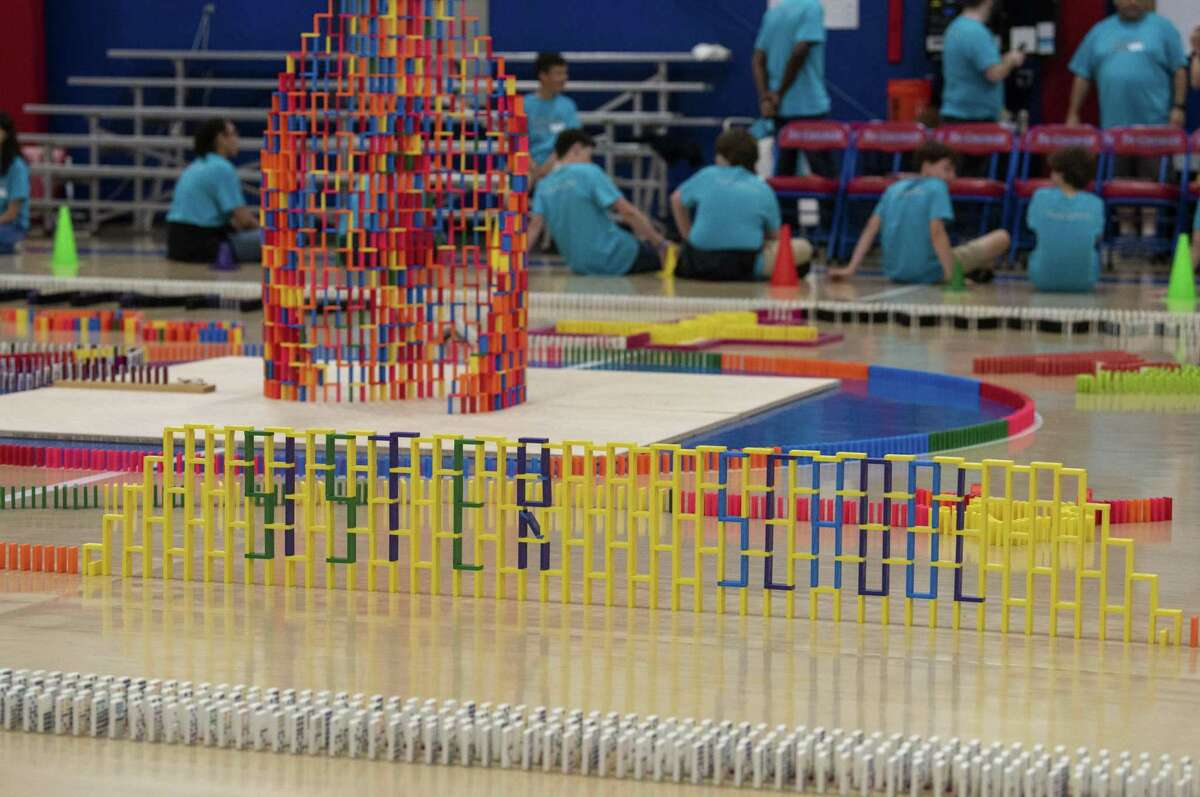 """Part of a complex pattern of more than 30,000 colorful dominoes sitting on the floor of the gym at St. George Episcopal School on Monday includes the words """"Sister School."""" Students at the San Antonio private school were marking the 14th year of their Chain of Love fundraiser, which benefits their sister school, St. Benoit, in Mombin Crochu, Haiti."""