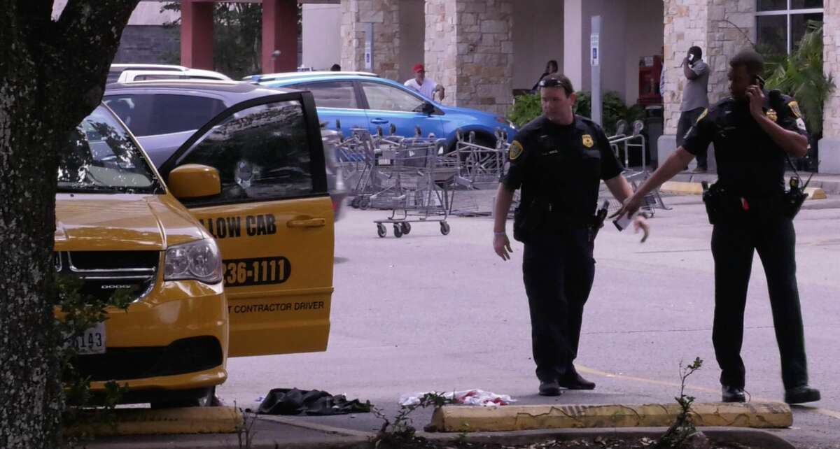 Houston police officer investigate a shooting after a taxi driver was shot outside the Kroger parking lot in the 3000 block of Montrose Boulevard on Monday, April 29, 2019.