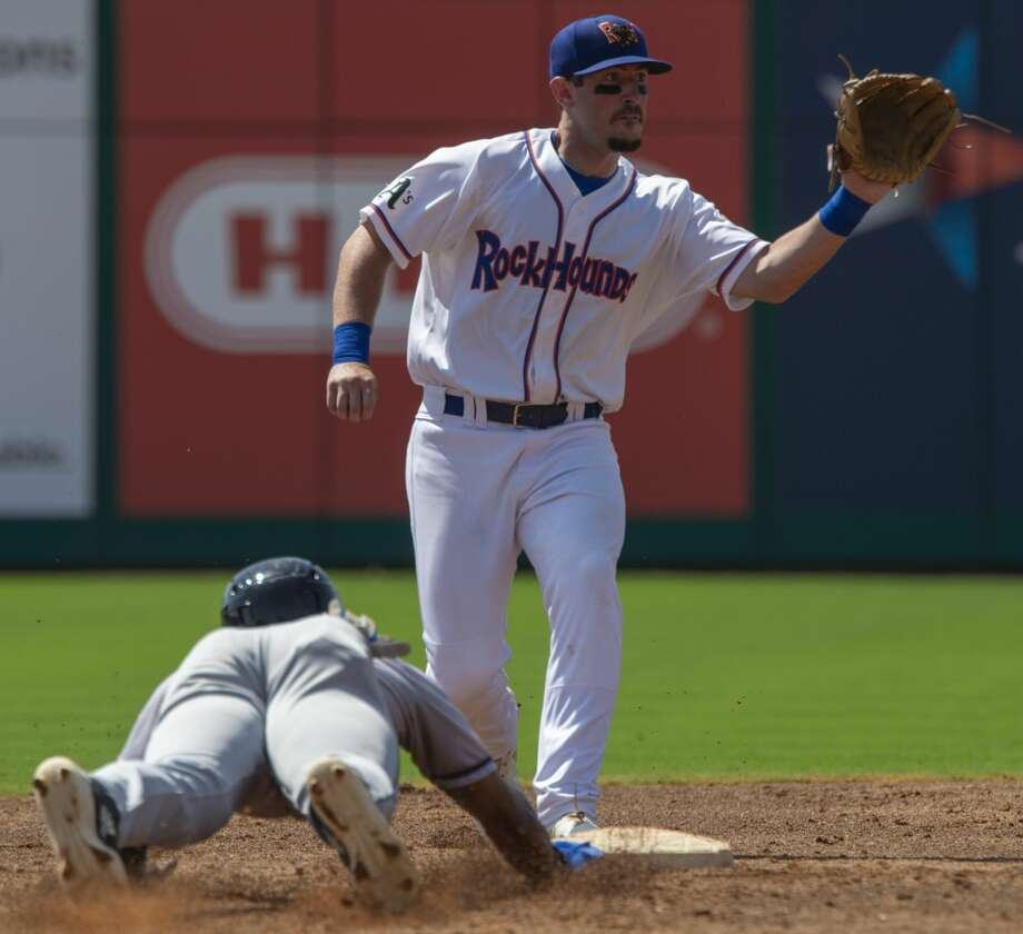 RockHounds' Mikey White looks for the ball on a pickoff attempt at second 04/29/19 as NW Arkansas' Nick Heath dives back safely at Security Bank Ballpark. Tim Fischer/Reporter-Telegram Photo: Tim Fischer/Midland Reporter-Telegram