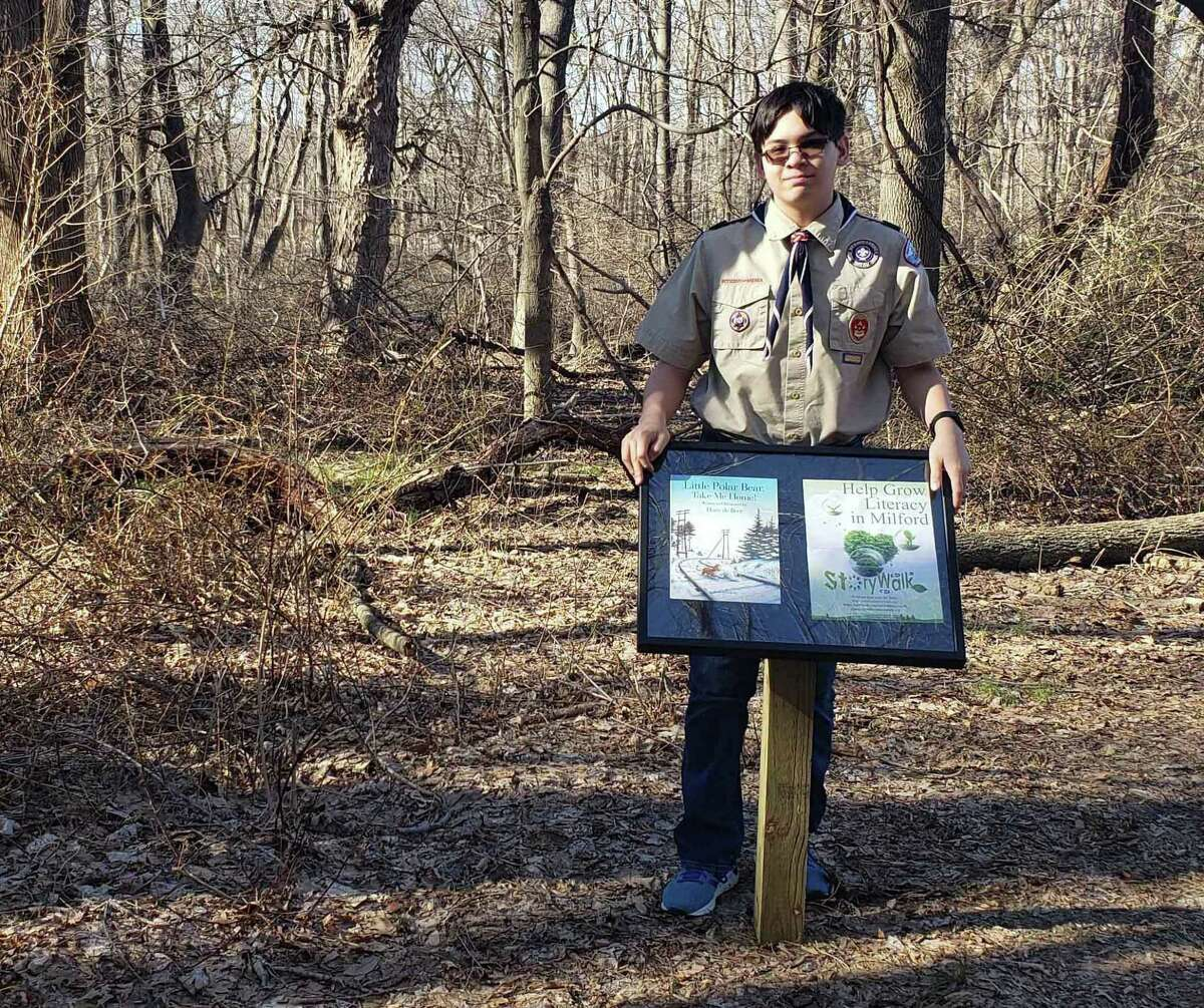 Marco Buschauer, a Scout with Troop 1 in Milford, stands with a sample of the 33 posts that will be set up at Eisenhower Park in Milford to create a StoryWalk.