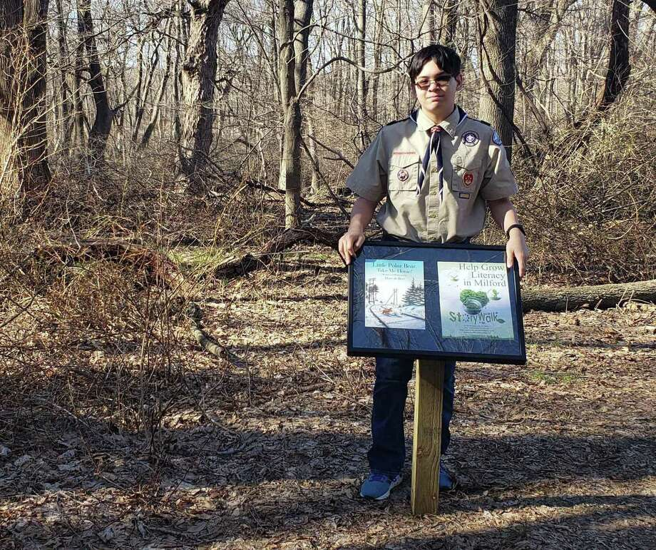 Marco Buschauer, a Scout with Troop 1 in Milford, stands with a sample of the 33 posts that will be set up at Eisenhower Park in Milford to create a StoryWalk. Photo: Marco Buschauer / Contributed Photo