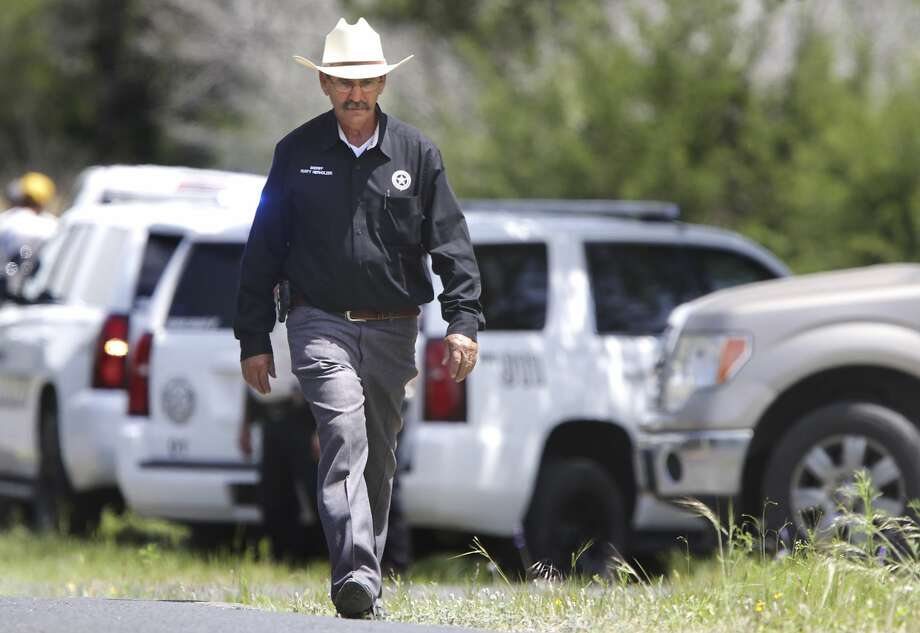Kerr County Sheriff Rusty Hierholzer walks along Sheppard Rees Rd, near the location where a small private plane crashed just outside Kerrville on privated land, on Monday, April 22, 2019. Photo: Bob Owen/Staff Photographer