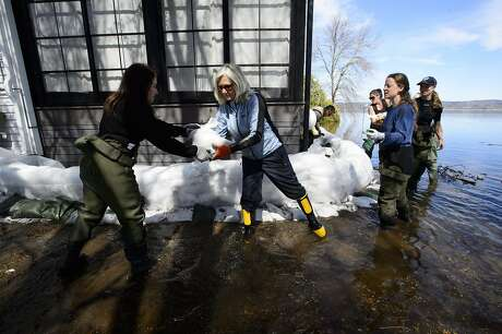 Residents, friends and volunteers work to hold back floodwaters on the Ottawa River in Constance Bay, Ontario, on Monday, April 29, 2019. (Sean Kilpatrick/The Canadian Press via AP)