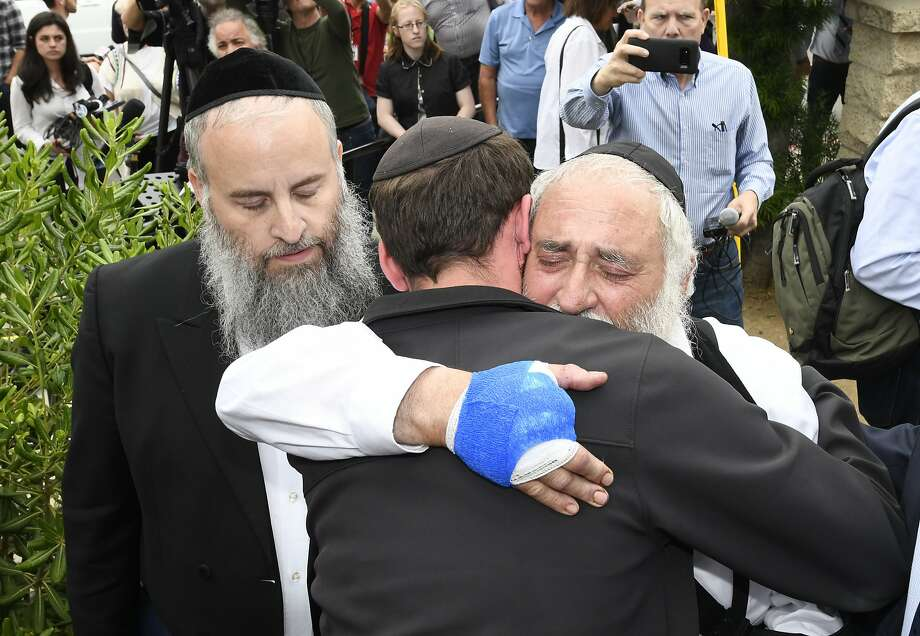 Rabbi Yisroel Goldstein, who was shot in the attack and lost a finger, hugs a well-wisher on Sunday. Photo: Denis Poroy / Associated Press