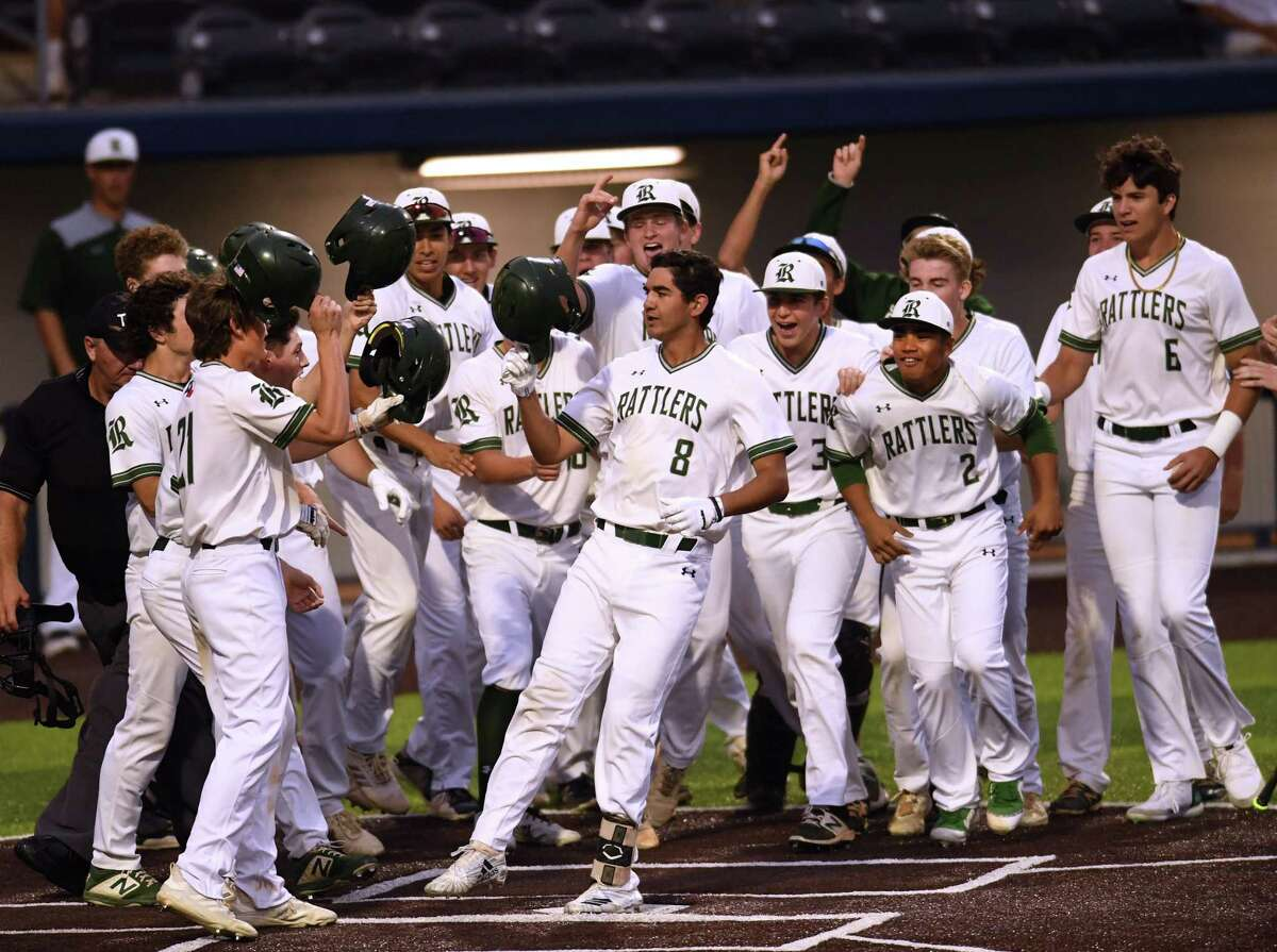 Reagan players greet Cal Martin (8) at the plate after his grand slam against MacArthur helped the Rattlers clinch the 27-6A title outright.