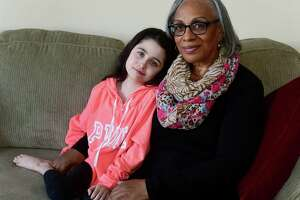 Jerlene Esaw and her adopted daughter Ashley Esaw, 12, in their home Tuesday, March 19, 2019, in Norwalk, Conn. Jerlene Esaw has fostered twenty children in the past including Ashely and has raised three children of her own.