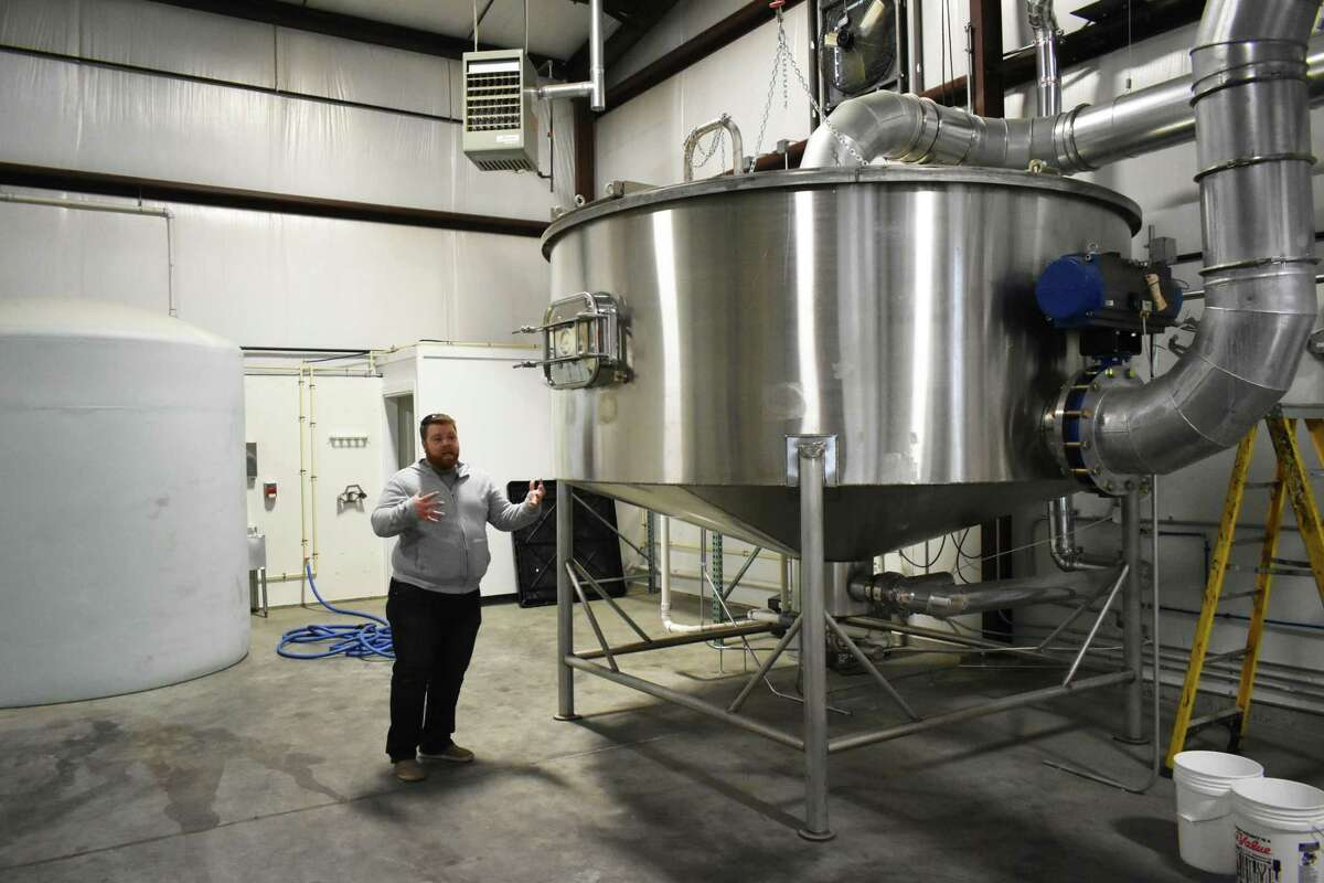 Rooster Malt co-founder James Tanner with a machine he designed to create malted barley, on 2nd Lane in Bethel, Conn.