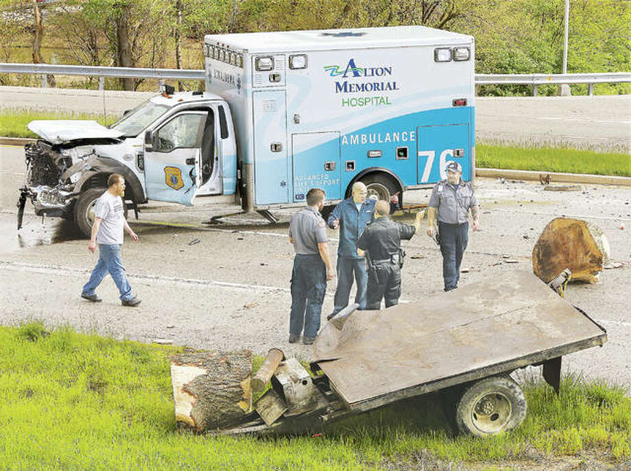 The Ford F-450 cab of an Alton Memorial Ambulance was heavily damaged Monday morning after it collided with a trailer full of heavy logs, being pulled behind a pickup truck, on Illinois Route 143 at the Cpl. Chris Belchik Memorial Expressway in Alton. The impact sent at least one log flying about 100-feet from the intersection. Nobody was injured but the paramedics on board were taken back to the hospital via another ambulance. EMS supervisors helped transfer drugs and life saving equipment off the brand new rig which cost more than $270,000. The crash closed the eastbound lanes of Illinois Route 143 for an hour, trapping dozens of motorists who had no where to turn around. It was unclear who was at fault or if any citations were issued in the crash, and a request for details from the Alton Police Department had not been returned Monday evening.