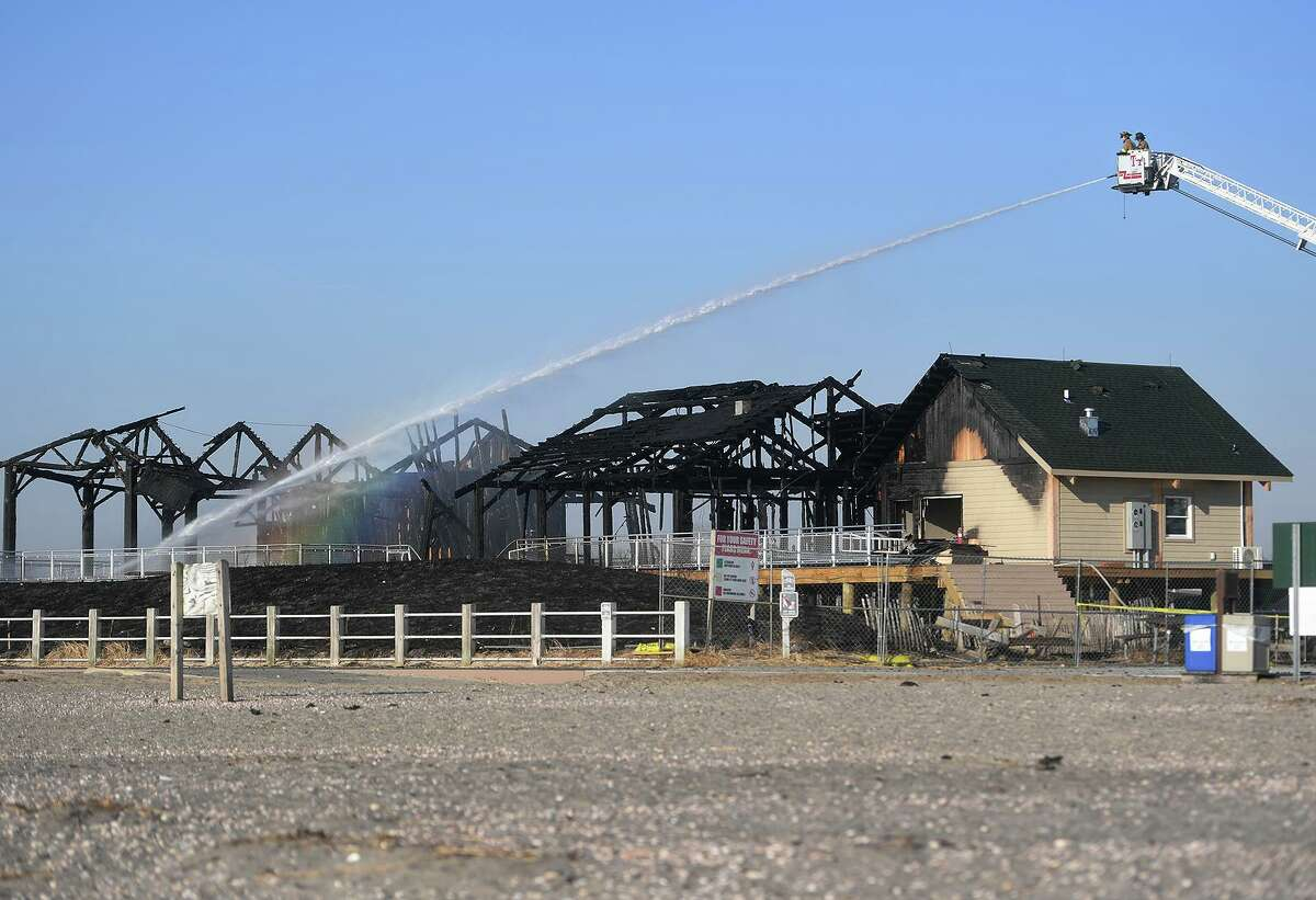 Milford firefighters pour water on remaining hot spots following a fire that destroyed the new pavilion, concessions, and bathrooms at Silver Sands State Park in Milford, Conn. on Wednesday, March 20, 2019. The fire started late Tuesday night, March 19, and was fully involved when firefighters arrived on scene.