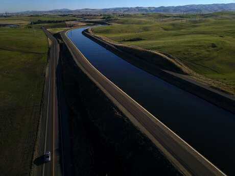 A car drives on Mountain House Road alongside the Governor Edmund G. Brown California Aueduct that carries water from the Sacramento-San Joaquin Delta outside Byron, Calif., to Southern California on Tuesday, December 11, 2018. On Wednesday, the Legislature is expected to vote on a massive water bill which could decide the fate of the state's water, pitting environmentalists and sportsmen against farmers and city dwellers. No matter how the vote goes, someone will be unhappy, either the cities and suburbs, or the ranchers/farmers or the environmentalists.