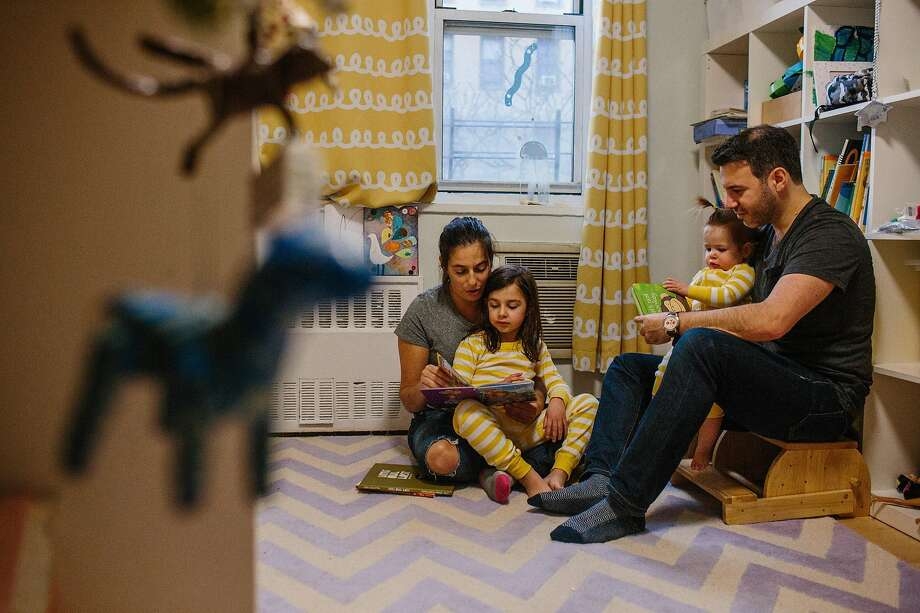 Matthew Schneid and Daniela Jampel read bedtime stories to their children. American women still face huge challenges in seniority and pay, which often leads to frustration. Photo: Gabriela Bhaskar / New York Times