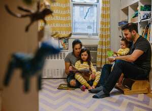 """Matthew Schneid and Daniela Jampel read bedtime stories to their children, in New York, March 27, 2019. American women of working age are the most educated ever. Yet it's the most educated women who face the biggest gender gaps in seniority and pay. """"The trade-off between time and money is not linear,"""" Jampel said. """"It took a long time to get myself to the point of accepting that."""" (Gabriela Bhaskar/The New York Times)"""