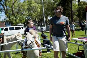 Mahayla Fisher rides a pony under the watch of her dad Dan Fisher at Alameda's Earth Day Festival at Washington Park in Alameda, Calif., on Saturday, April 20, 2019.