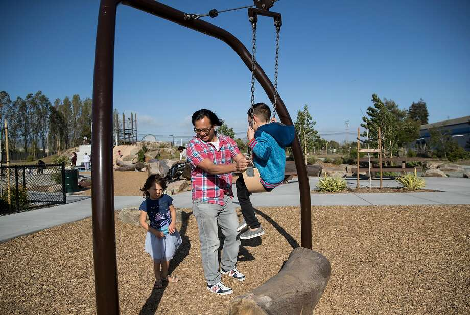 A family plays on the playground at the Jean Sweeney Open Space Park in Alameda. The park, located on land previously belonging to the Alameda Belt Line Railroad, is the city's largest and was 20 years in the making. Photo: Laura Morton