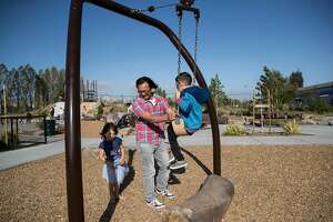 A family plays on the playground at the Jean Sweeney Open Space Park in Alameda, Calif., on Saturday, April 20, 2019. The park, located on land previously belonging to the Alameda Belt Line Railroad, is the city's largest and was 20 years in the making.