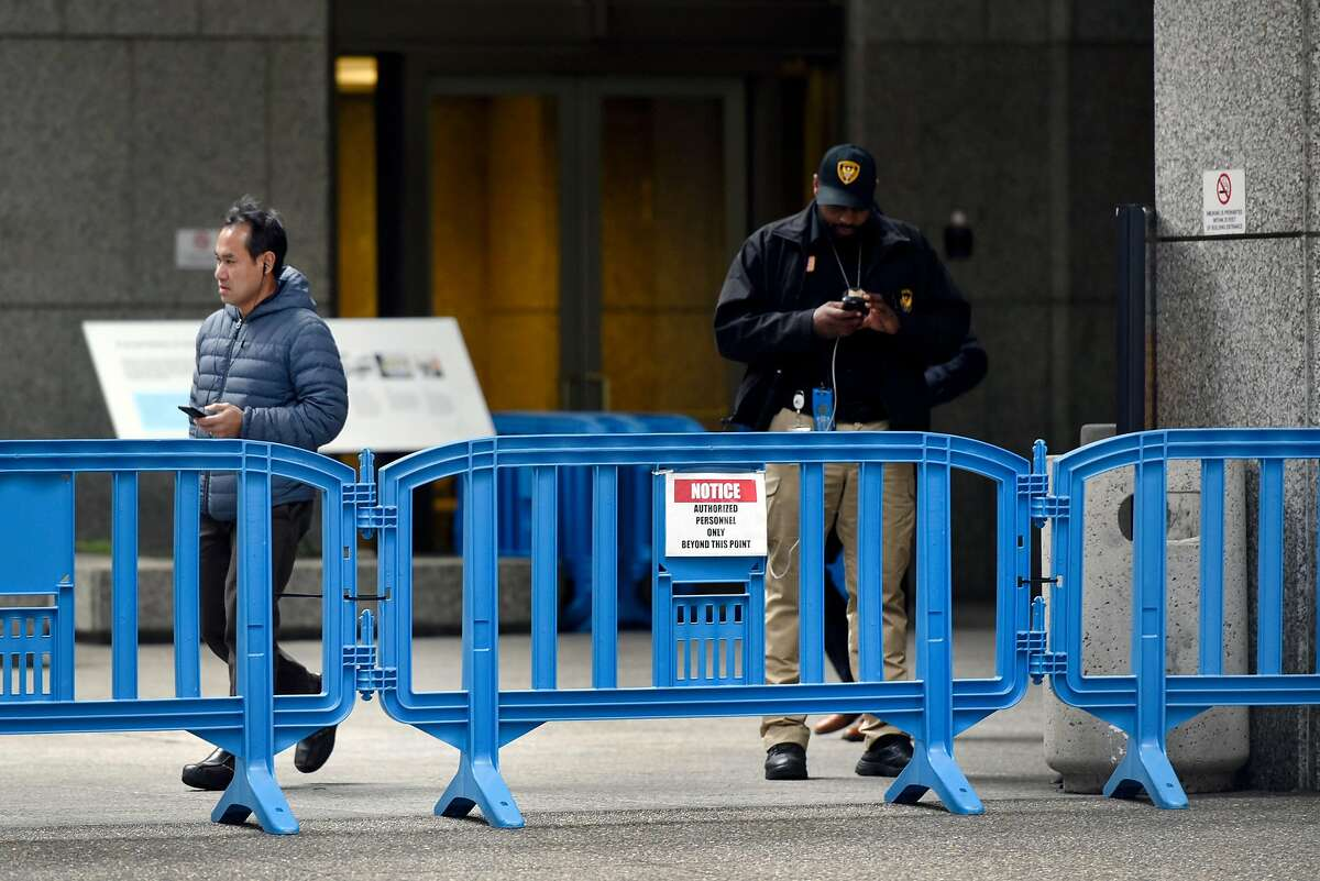 A security guard stands behind a barricade outside of PG&E's headquarters in San Francisco, CA, on Monday January 14, 2019.