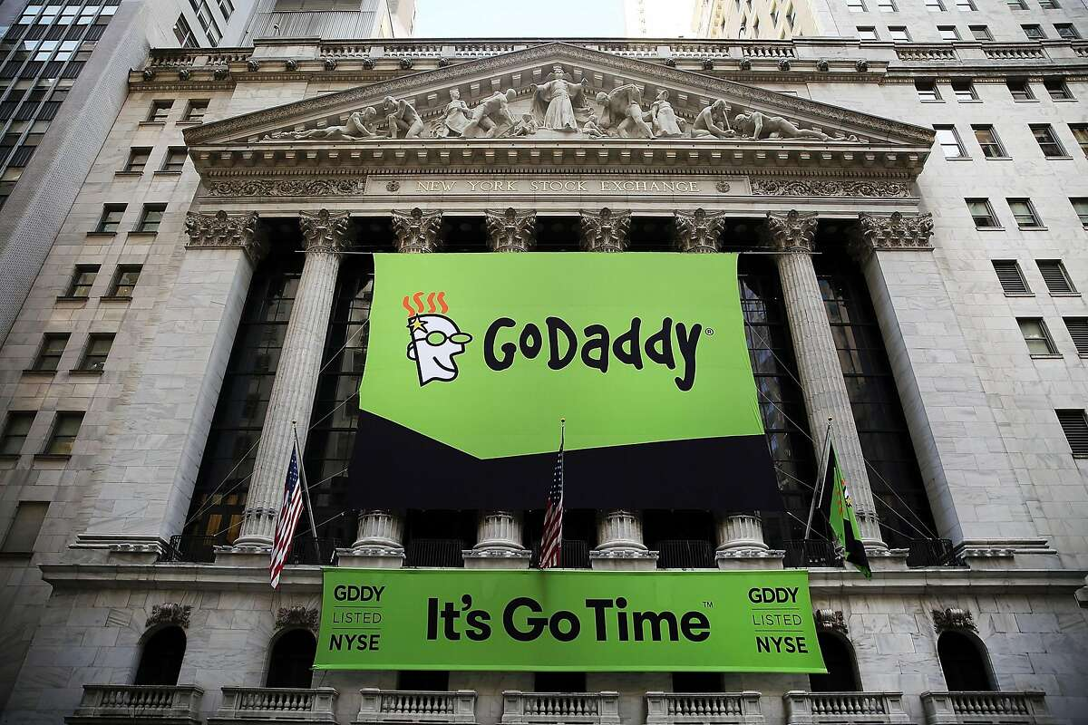 """NEW YORK, NY - APRIL 01: The GoDaddy banner hangs outside of the New York Stock Exchange as the website hosting service makes its initial public offering (IPO) on April 1, 2015 in New York City. GoDaddy, which manages about a fifth of the world's Internet domains will list on the New York Stock Exchange under the ticker """"GDDY"""" and priced its IPO at $20 Tuesday night. (Photo by Spencer Platt/Getty Images)"""