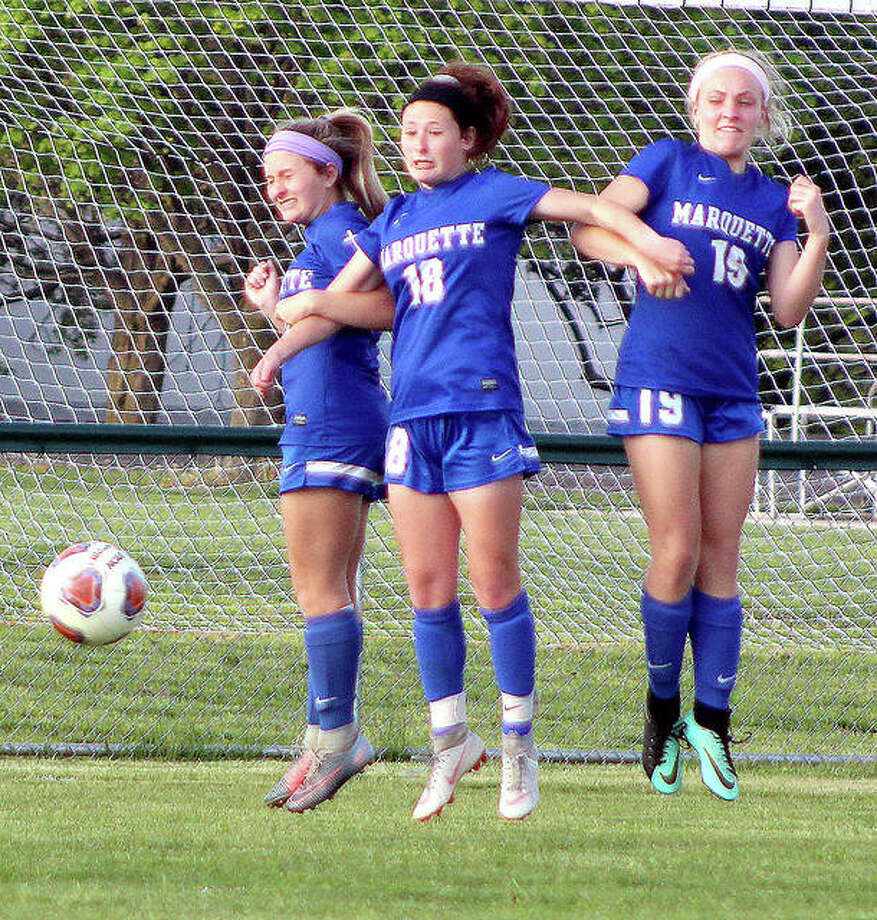 From left, Marquette's Lydia Randazzo, Madelyn Smith and Amma Anselm leap with arms locked together as they form a defensive wall during a Belleville East free kick late in Monday's 3-1 Marquette victory at Gordon Moore Park. Photo: Pete Hayes | The Telegraph