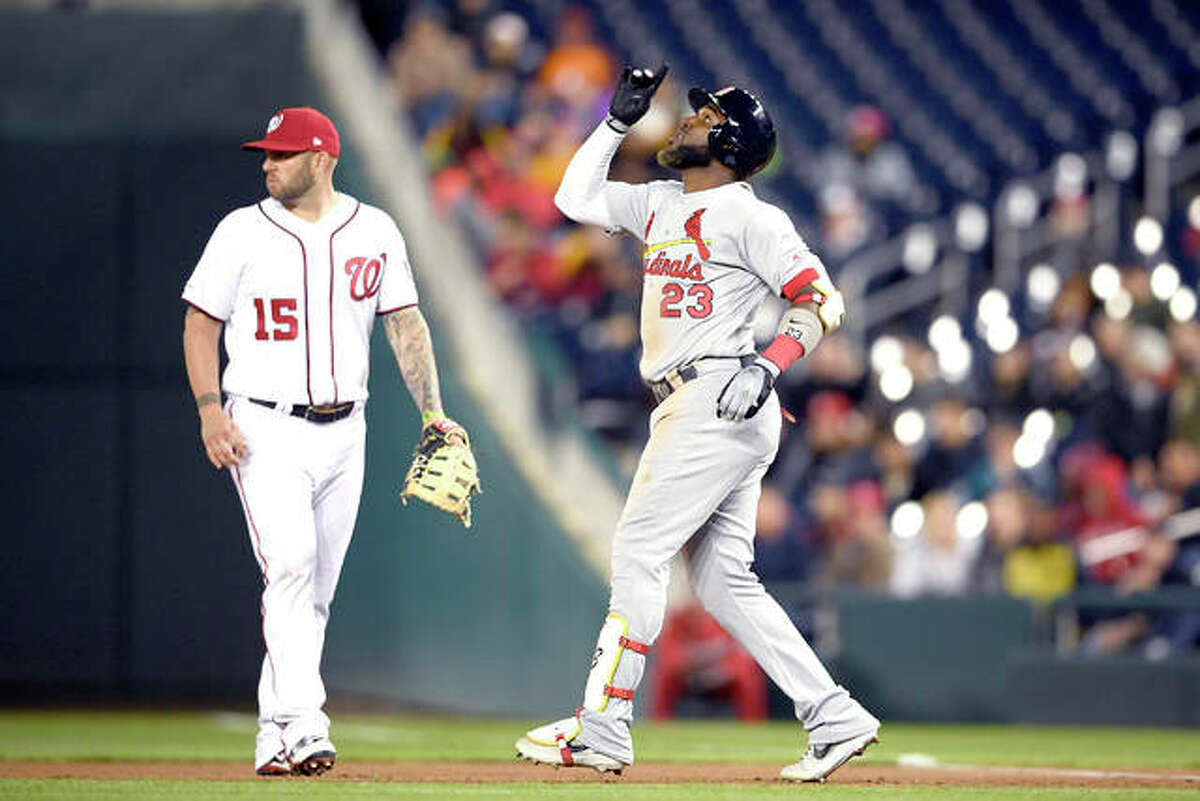 The Cardinals' Marcell Ozuna (23) reacts next to Nationals first baseman Matt Adams (15) after hitting a single in the seventh inning of Monday's game in Washington.