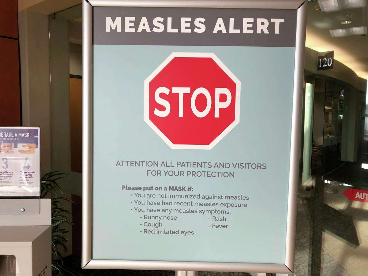 FILE - In this Jan. 30, 2019, file photo, a sign warning patients and visitors of a measles outbreak is shown posted at The Vancouver Clinic in Vancouver, Wash. Officials in the Pacific Northwest say a measles outbreak that sickened multiple people is over. (AP Photo/Gillian Flaccus, File)