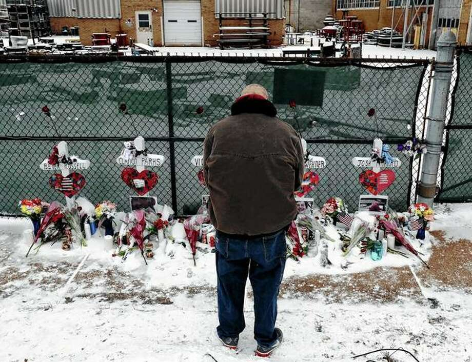 """A man prays Feb. 17 at a makeshift memorial placed for five victims near the warehouse of Henry Pratt Co. in Aurora. A report on the February shooting at the manufacturing plant found that the man who killed five people after he was fired told another employee that, if he lost his job, he would kill other workers and """"blow police up."""" The Kane County State's Attorney's office report released Monday says the other Henry Pratt Co. employee didn't report Gary Martin's comments to superiors because Martin routinely made """"off the wall"""" statements and that he didn't believe Martin would do anything violent. Photo: Nam Y. Huh 