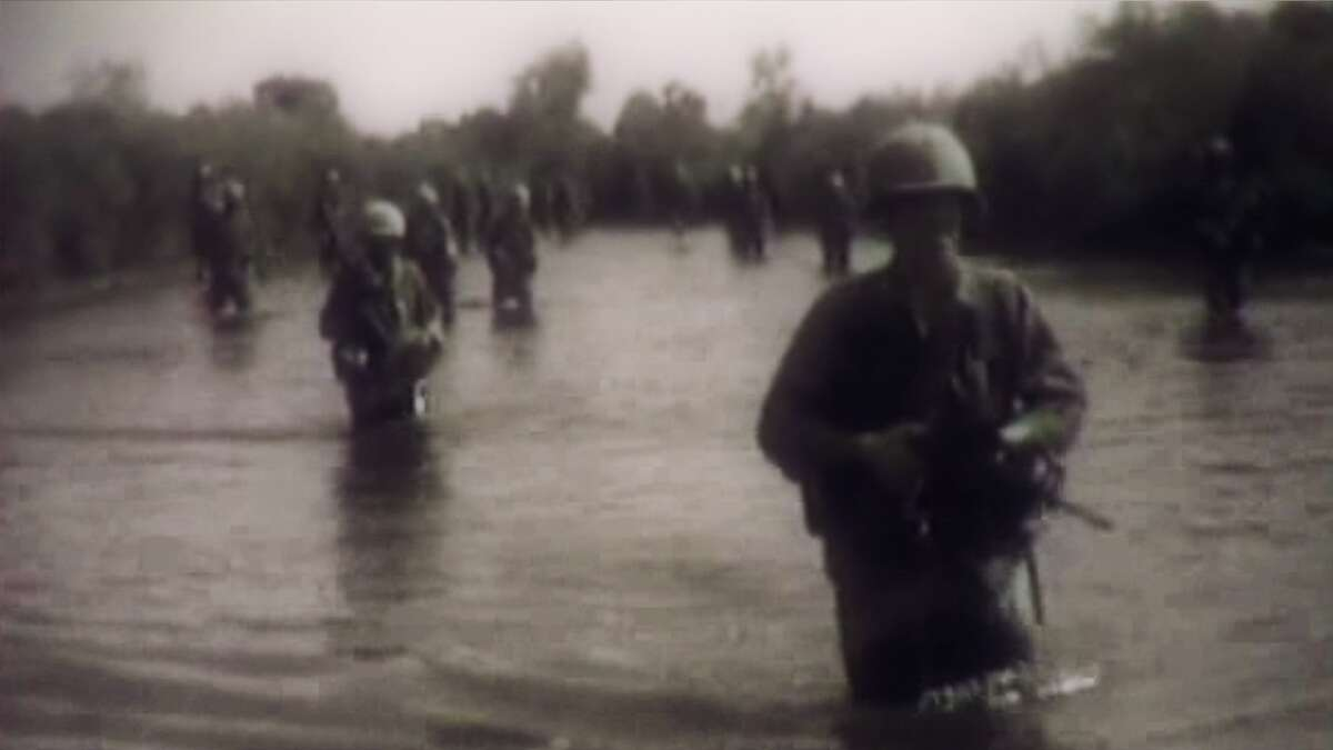 Image of American soldiers crossing a river during the Vietnam, featured in