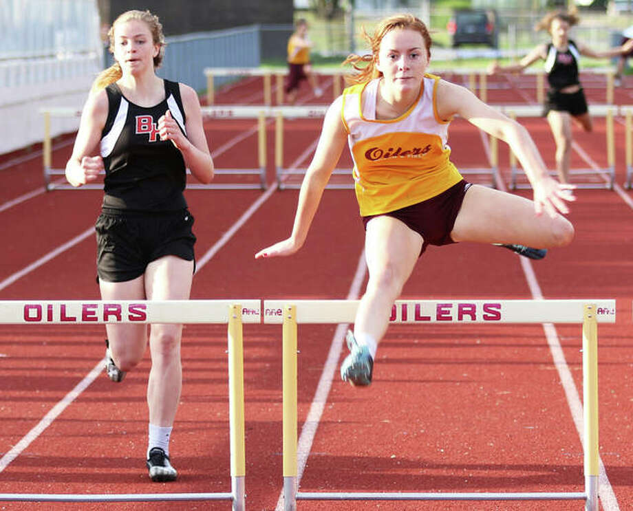 EA-WR's LeighAnn Nottke (right) clears the final hurdle ahead of Bunker Hill's Makenna Wilkinson in the 300-meter hurdles Monday at the Prairie State Conference Track Meet at Memorial Stadium in Wood River. Nottke won the race, with Wilkinson placing second. Photo: Greg Shashack / The Telegraph