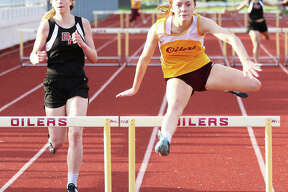 EA-WR's LeighAnn Nottke (right) clears the final hurdle ahead of Bunker Hill's Makenna Wilkinson in the 300-meter hurdles Monday at the Prairie State Conference Track Meet at Memorial Stadium in Wood River. Nottke won the race, with Wilkinson placing second.