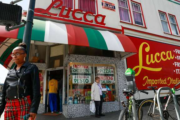 People pass by Lucca Ravioli on it's final day open after 90 years of business on Valencia Street in San Francisco, California, on Tuesday, April 30, 2019.