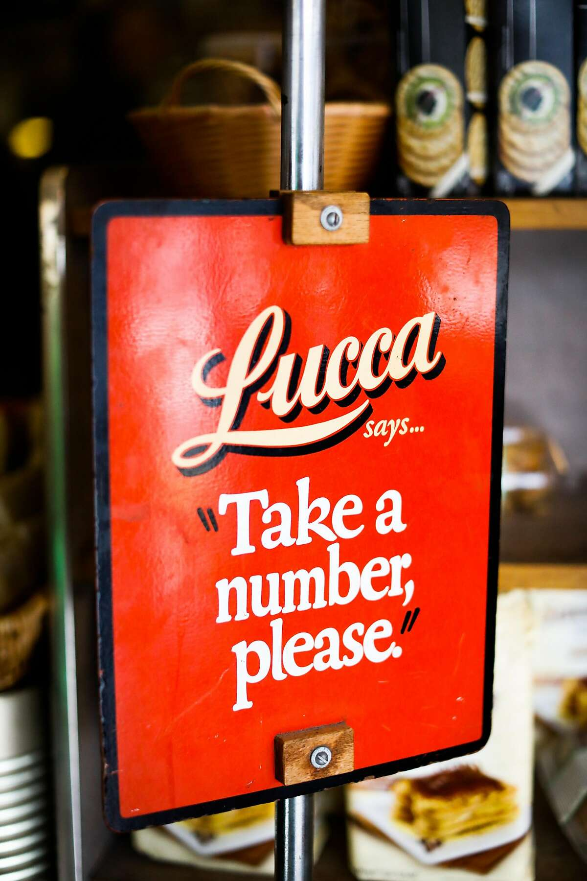A sign for customers to take a number is seen at Lucca Ravioli on it's final day open after 90 years of business on Valencia Street in San Francisco, California, on Tuesday, April 30, 2019.