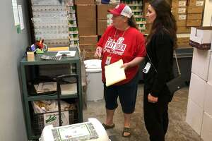 """Brenda Martin, right, and Carrie Singletary weigh donated food on Wednesday, April 24, 2019, as part of the """"Milk 4 Many"""" program. Martin is asubstitute teach at Katy Elementary School and volunteer for the """"Milk 4 Many"""" program. Singletary ishead of the Parent Teacher Organization at Katy Elementary."""