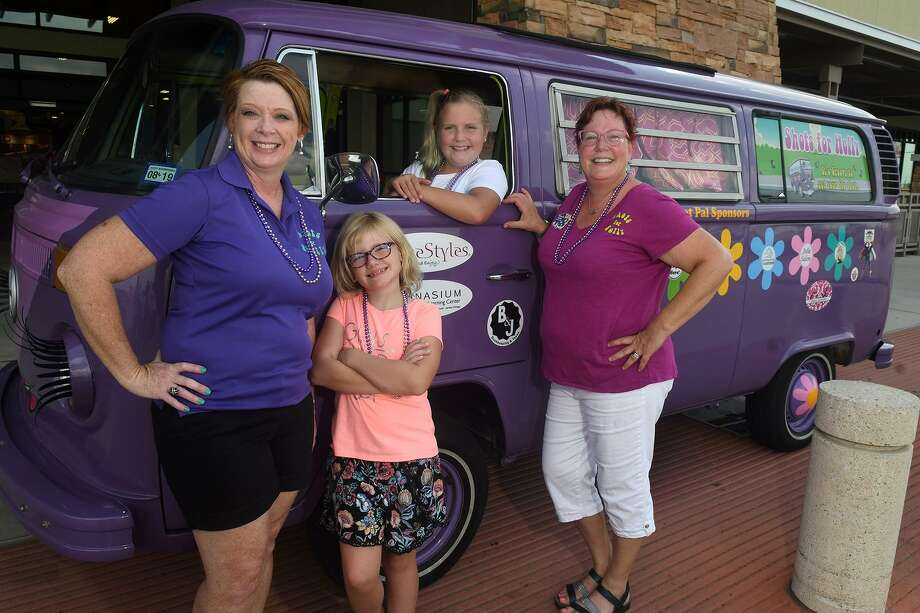 Shots for Holly crew member Nicole Travis, from left, her daughter Addison, 8; Bailey Sessions, 12; and Michelle Becker, Shots for Holly founder and Bailey's mom, show off their ride during a trip to the H-E-B at 9722 Fry Road in Cypress where they hoped to encourage people to get their flu shots. Photo: Jerry Baker, Houston Chronicle / Contributor / Houston Chronicle