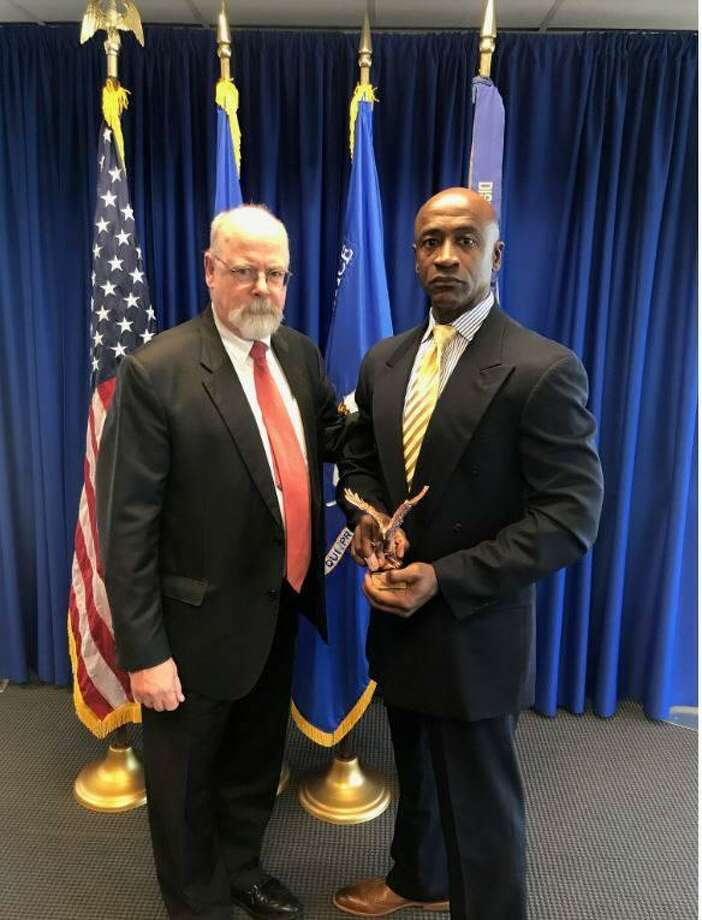 Connecticut U.S. Attorney John Durham (r) giving a community policing award to Stamford police officer Silas Redd this week. jRedd and 13 other officers from around the state were congratulated for their work in their local communities at a ceremony at Durham's New Haven office on Tuesday. Photo: Stamford Police / Contributed