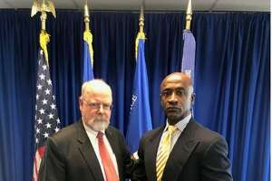 Connecticut U.S. Attorney John Durham (r) giving a community policing award to Stamford police officer Silas Redd this week. jRedd and 13 other officers from around the state were congratulated for their work in their local communities at a ceremony at Durham's New Haven office on Tuesday.