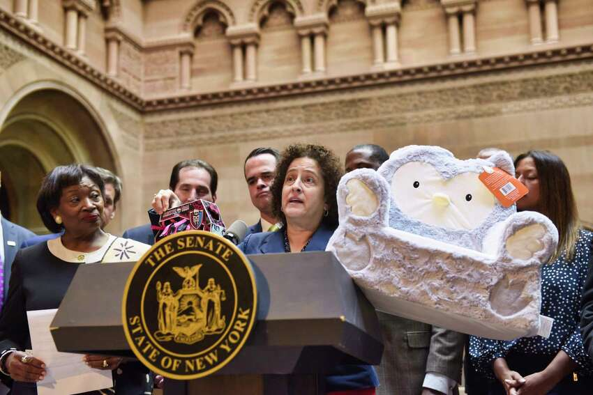 Kathy Curtis, executive director of Clean and Healthy New York, holds up two children's toys that she says contain substances harmful to children at a press event held by the New York State Senate majority at the Capitol on Tuesday, April 30, 2019, in Albany, N.Y. The Senate majority held the event to talk about their legislation to protect New Yorkers against toxic materials, establish a Constitutional right to clean air and water, and to protect the state?•s environment and natural resources. (Paul Buckowski/Times Union)