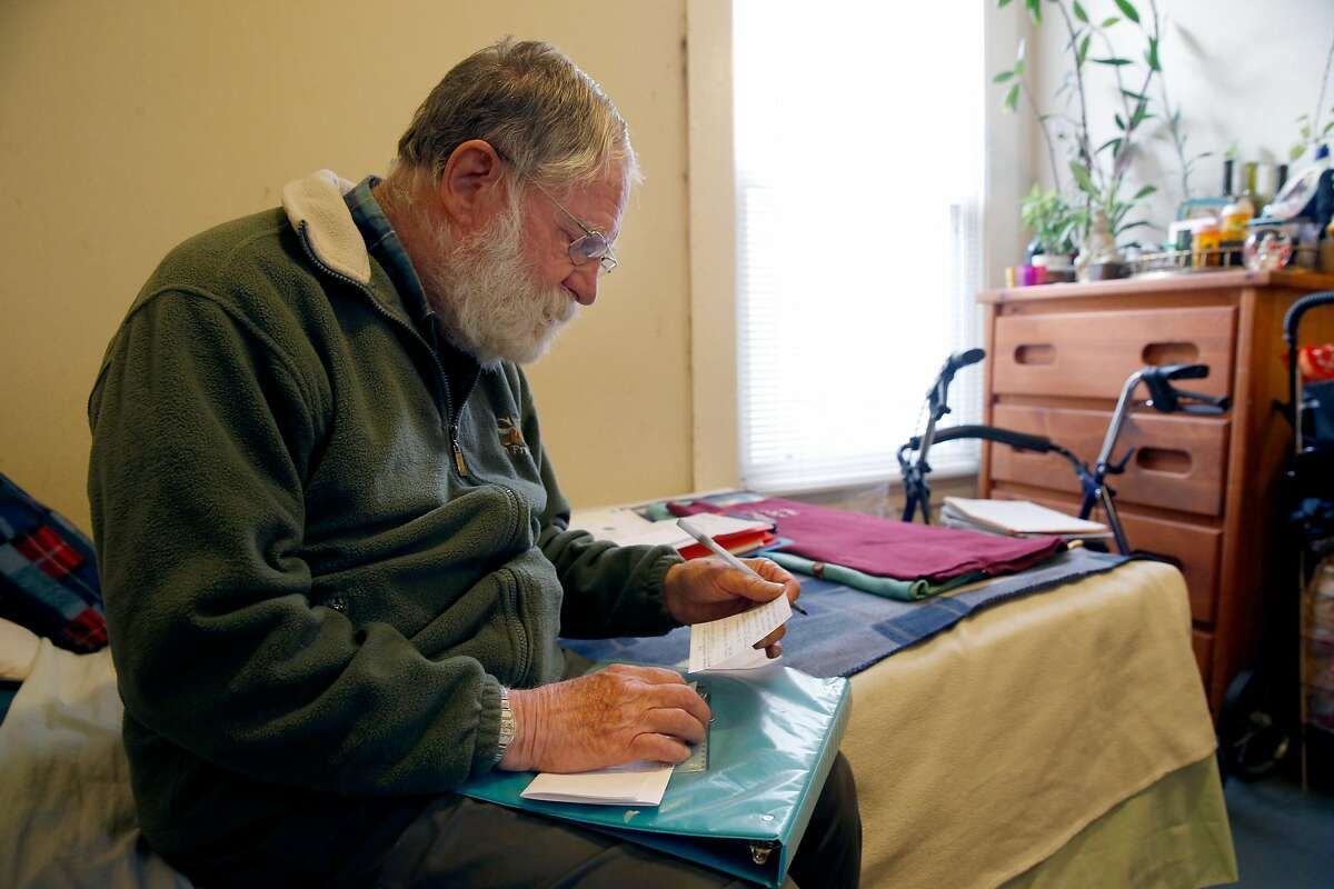 Melvin Beetle reviews documents in his South of Market room in San Francisco, Calif. on Tuesday, April 30, 2019. Beetle will finally be able to qualify for CalFresh benefits in June which will assure him of three meals a day.