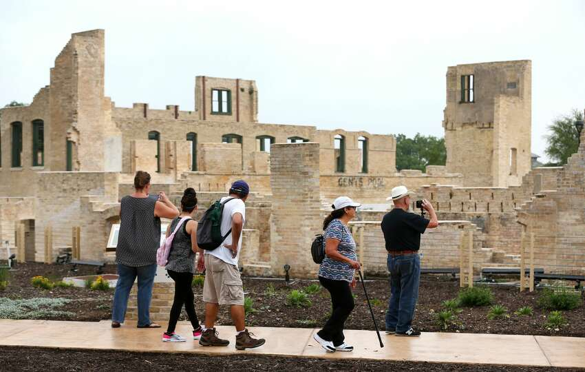 People walk Tuesday, April 30, 2019 past the former Hot Wells Hotel during the grand opening of the Hot Wells of Bexar County park. The once-crumbling building has been stabilized by Bexar County as part of turning the approximately four acre site into a park which is connected to the Mission Reach section of the San Antonio River Walk.
