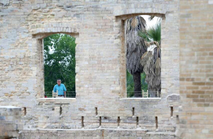 A person looks Tuesday, April 30, 2019 through a former window of the now stabilized Hot Wells Hotel ruins which are the centerpiece of the just opened Hot Wells of Bexar County park.
