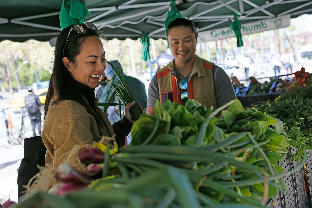 From left: Nini Gueco and Kevin Gueco shop for produce at Green Thumb at the Ferry Plaza Farmers Market on Tuesday, April 30, 2019, in San Francisco, Calif. Starting May 1, people who receive Supplemental Security Income (SSI) are eligible to apply for CalFresh. Among the places they can be redeemed is the Ferry Plaza Farmers Market.
